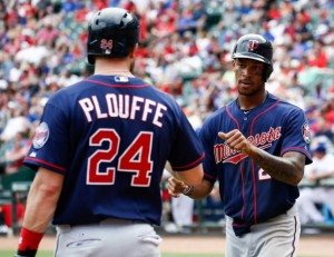Buxton congratulated by Plouffe after scoring what turns out to be the winning run  in his first big league game.
